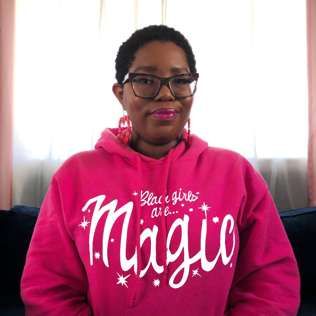 """Dominique wearing a """"Black Girls Are Magic"""" Hoodie while sitting on a dark blue sofa. In front of a window with white curtains. Pink drapes on the edges."""
